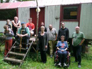 Mitglieder der grünen, darunter Claudia Kalish und Bewohner*innen des Wohnprojektes Unfug stehen vor einem Bauwagen. eine Person stitzt im Rollstuhl